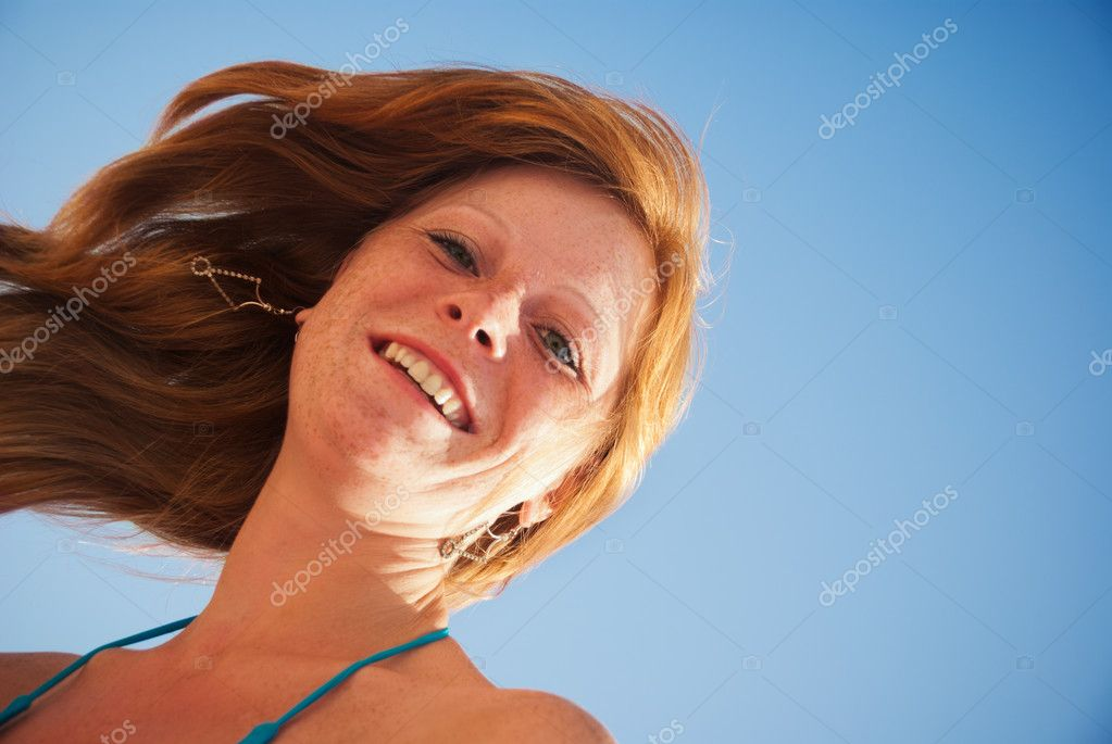 Happy beautiful natural red-haired girl against the blue sky — Stock Photo #6435171