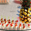 Pineapple and strawberries on skewers - Stock Photo