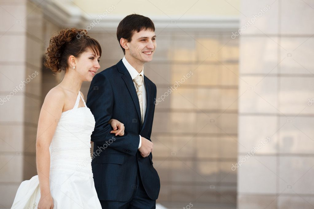 Newlyweds walking. Wall on the background — Stock Photo #5743638