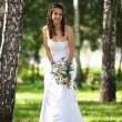 Beautiful smiling bride in the park - Stock Photo