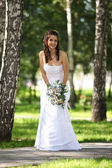 Beautiful smiling bride in the park — Stock Photo