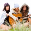 Royalty-Free Stock Photo: Young Women at the Beach With a Guitar