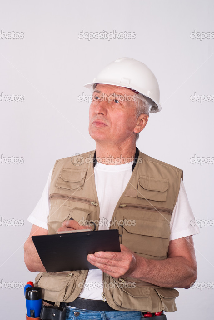 Senior builder writing a list on white  Foto Stock #5766776
