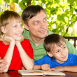 Boys and dad reading - Stock Photo