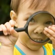 Little girl and loupe - Stock Photo