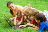 Family with laptop on grass — Stock Photo