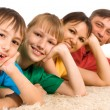 Cute family lying on carpet — Stock Photo