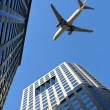 Beijing: plane over modern buildings - Stock Photo