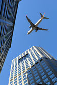 Beijing: plane over modern buildings — Stock Photo