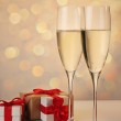 Glasses of champagne with red ribbon gifts — Stock Photo #5723067
