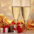 Glasses of champagne with red ribbon gifts — Stock Photo