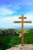 Christian cross at mountain top — Stock Photo