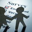 Survey and Paper Chain Men - Stock Photo