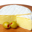 Wheel of cheese with green olives. - Stock Photo