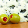 Close-up of green olives and blue cheese. - Stock Photo