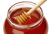 Wooden dipper with jar of honey. — Stock Photo