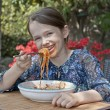 Girl is eating spaghetti — Stock Photo