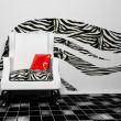 A blask and white armchair with a red pillow - Stock Photo