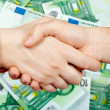 Handshake and money — Stock Photo