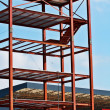 Steel Structure and Construction crane set against a blue sky - Stockfoto