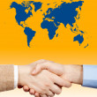 Business handshake under the world — Stock Photo