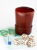Dices and leather thrower with money — Stock Photo