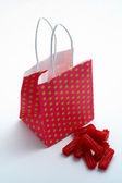 Red shopping bag and pieces of red licorices — Стоковое фото