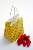 Yellow shopping bag and pieces of red licorices — Стоковое фото