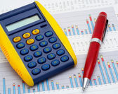 Calculator and pen on earnings chart — Stock Photo