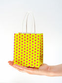Holding shopping yellow bag — Stock Photo