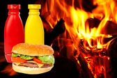 Burger over a flames background — Stock Photo