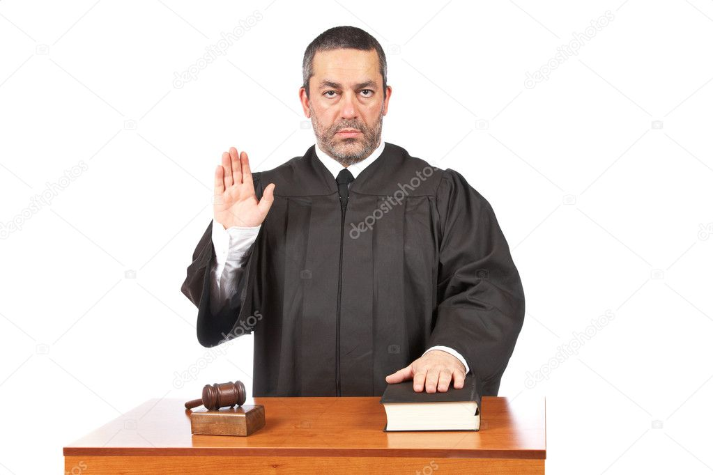 A serious male judge taking oath in a courtroom, isolated on white background. Shallow depth of field  Stock Photo #5881370