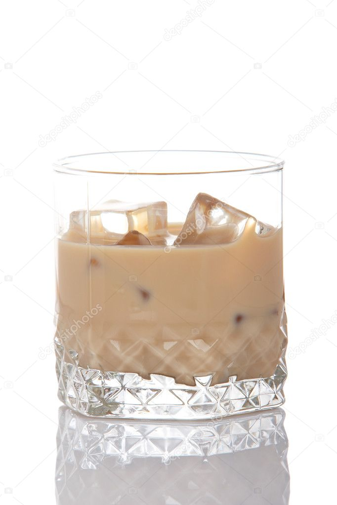 A whiskey cream glass with ice cubes, reflected on white background    #6339968