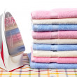 Electric iron and towels stacked — Stock Photo