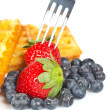 Waffles, blueberries and the fork pricking the strawberry — Stock Photo
