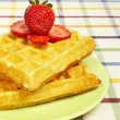 Waffles and strawberries on green plate - ストック写真