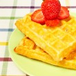 Waffles and strawberries on green plate - Stock Photo