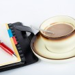 Close-up of a cup of coffee with the spoon inside and notebook with ballpoi — Stock Photo