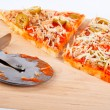 Detail of slices Italian pizza and cutter — 图库照片