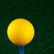 Stock Photo: Yellow golfball and blue tee