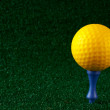 Yellow golfball and blue tee — Stock Photo