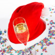 Champagne glass and christmas hat with ribbons — Stock Photo