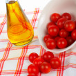 Oil bottle and tomatos cherry — Stock Photo