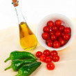Oil bottle, red tomatos cherry and green pepper — Stock Photo