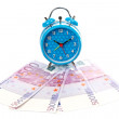 Alarm clock over a fan of money - Foto Stock