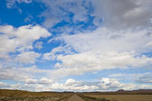 Lonely road under cloudy sky — Stock Photo