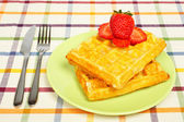 Waffles and strawberries on green plate — Stock Photo