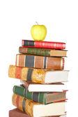 Yellow apple on pile of books — Stock Photo