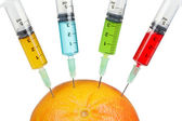 Grapefruit with four syringes — Stock Photo