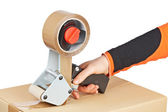 Packaging tape dispenser and shipping box — Stock Photo